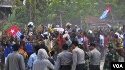 Para anggota Polri melepaskan tembakan peringatan saat beberapa warga Papua melakukan unjuk rasa dengan mengibarkan bendera Bintang Kejora di kabupaten Timika (1/12).