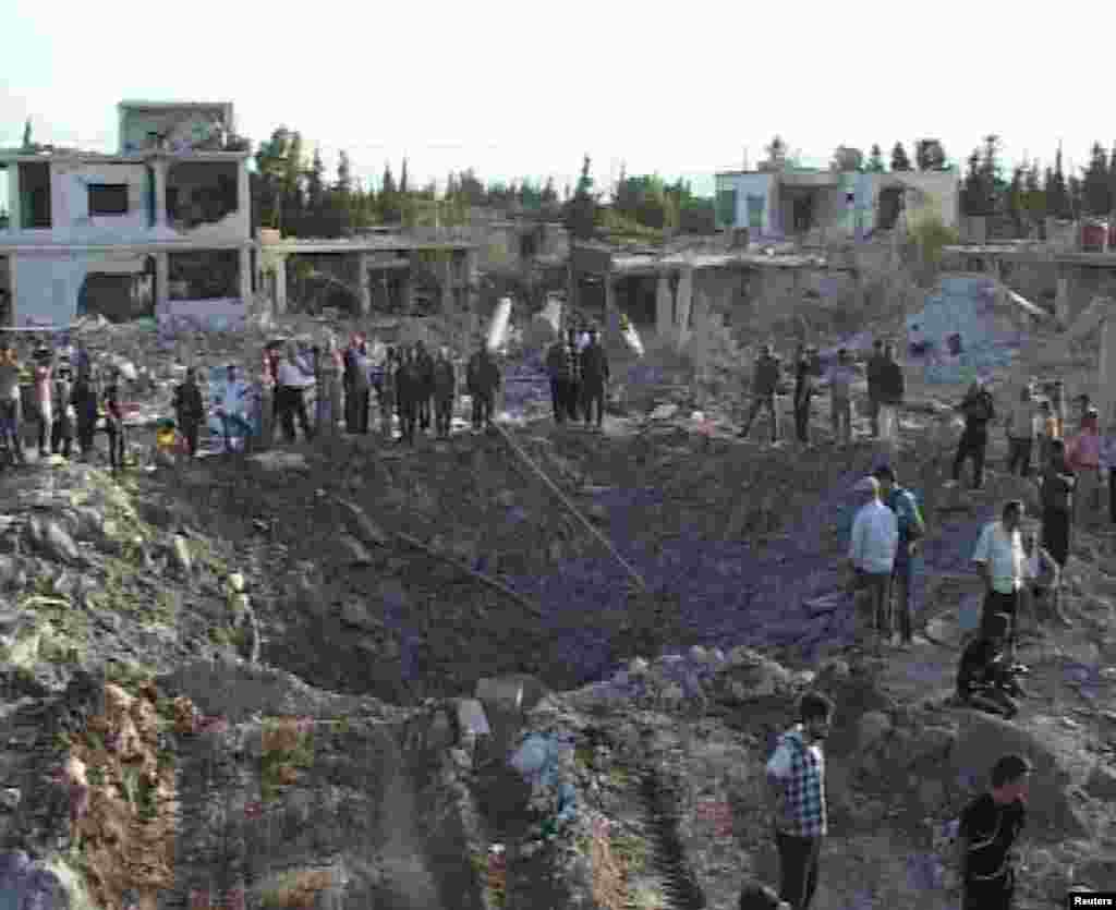 People gather around a crater in Hama city, Syria June 20, 2014, in this picture released by Syria's national news agency SANA.