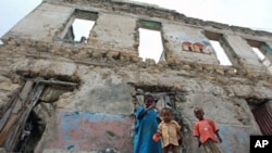 Internally displaced children stand outside a decrepit building they are using as a temporary home in the Hodan district of Somalia's capital Mogadishu