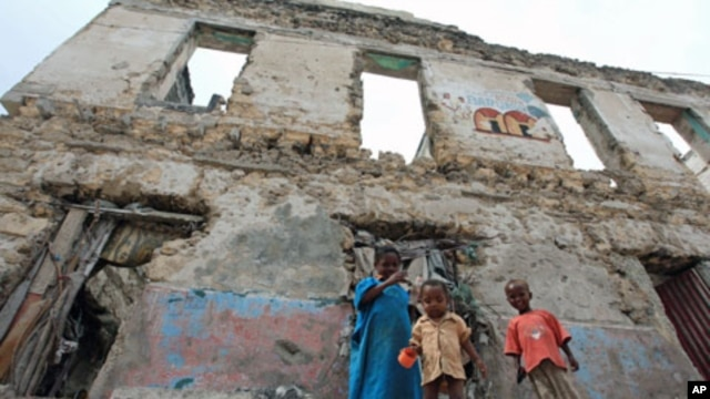 Internally displaced children stand outside a decrepit building they are using as a temporary home in the Hodan district of Somalia's capital Mogadishu, September 6, 2011.
