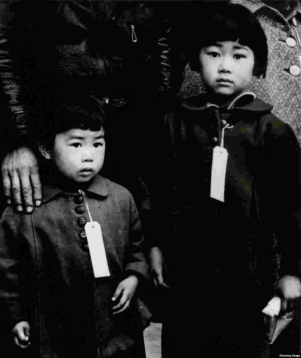 """Enforcement of Executive Order 9066: Japanese Children Made to Wear Identification Tags"" by Dorothea Lange, Hayward, California, 1942 (Photo credit: The Bancroft Library, University of California, Berkeley)"