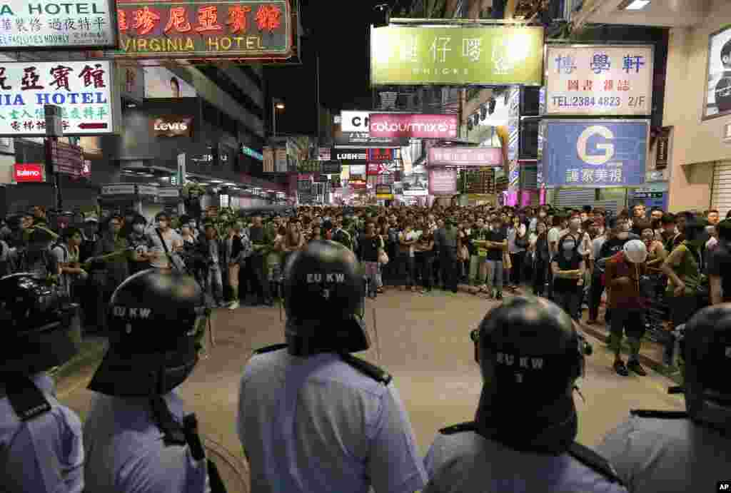 Riot police officers stand guard at a main road in the Mong Kok district of Hong Kong, Oct. 17, 2014. New scuffles broke out Friday night between police and pro-democracy activists in district where police cleared protesters earlier in the day.