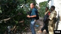 El periodista de la VOA, Peter Heinlein en agosto de 2011 investigando los restos del Black Hawk caído cerca de Mogadishu, Somalia. (VOA Photo/G. Joselow)