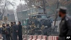 Petugas keamanan Turki dan Afghanistan menginspeksi kendaraan yang rusak akibat bom bunuh diri di Kabul, Afghanistan (26/2). (AP/Rahmat Gul)