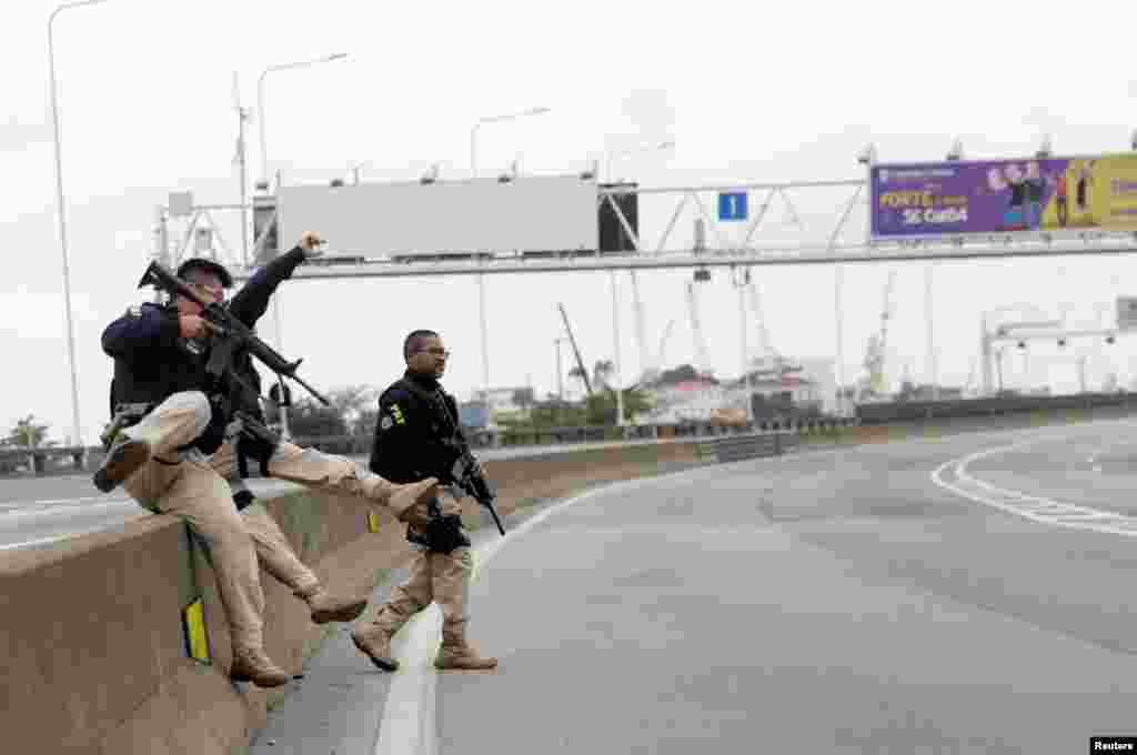 Federal police officers are seen at the Rio-Niteroi Bridge, where armed police surrounded a hijacked passenger bus in Rio de Janeiro, Brazil.