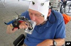 Cuplikan video tidak bertanggal ini menunjukan seorang pasien yang menggunakan lengan robot untuk minum dari gelas di Badalona, Spanyol.