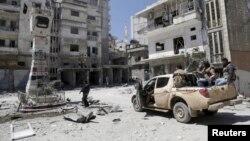 Tentara pemberontak Suriah memeriksa kerusakan akibat serangan pasukan pemerintah di Jisr al-Shughour (26/4).