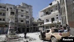 시리아 반군 병사들이 26일, 정부군의 공습으로 파괴된 것으로 알려진 지역을 조사하고 있다.