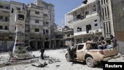 敘利亞反叛武裝4月26日在政府軍機空襲後巡視一個城鎮的破壞情況