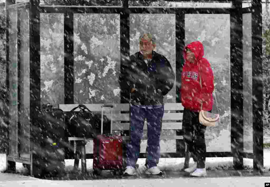 A couple stands in a bus shelter during a snowfall in Dover Township, New Jersey, November 7, 2012, as the region pounded by Superstorm Sandy last week is hit by a Nor'Easter.