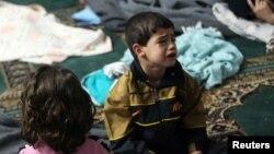 Seorang anak laki-laki yang bertahan dari apa yang para aktivis sebut serangan gas menangis di tempat penampungan di dalam masjid di Durma, Damaskus (21/8). (Reuters/Mohamed Abdullah)