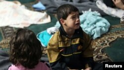 Seorang anak yang selamat dari serangan gas menangis di dalam tempat peampungan di sebuah masjid di wilayah Duma, Damaskus (21/8).