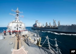 FILE - Guided-missile destroyer USS Bulkeley participates in a replenishment-at-sea with fleet replenishment oiler USNS John Lenthall in the Gulf of Oman. Iranian naval vessels conducted rocket tests last week near the USS Harry S. Truman aircraft carrier.