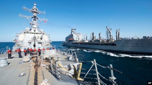 FILE - Guided-missile destroyer USS Bulkeley participates in a replenishment-at-sea with fleet replenishment oiler USNS John Lenthall in the Gulf of Oman. Iranian naval vessels conducted rocket tests last week near the USS Harry S. Truman aircraft carrier