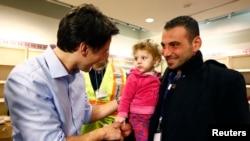 ອົບພະຍົບຊີເຣຍ ຖືກຕ້ອນຮັບ ໂດຍນາຍົກການາດາ ທ່ານ Justin Trudeau (ຊ້າຍ) ເວລາເຂົາເຈົ້າເດີນທາງໄປເຖິງ ສະໜາມບິນນາໆຊາດ Pearson ທີ່ນະຄອນ Toronto. (11 ທັນວາ 2015)