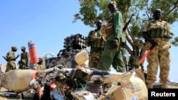 South Sudan army soldiers stand next to a destroyed motorcycle near Bor Airport, northwest of capital Juba on December 25, 2013.