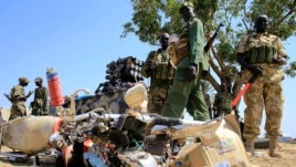 South Sudan army soldiers stand next to a destroyed motorcycle near Bor airport on Dec. 25, 2013. The government says it has recaptured Bor from opposition fighters.