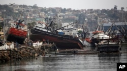 Boats lifted by an earthquake-triggered tsunami sit on a dock in Coquimbo, Chile, Sept. 18, 2015.