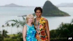 FILE - U.S. first lady Michelle Obama poses with Laureen Harper, spouse of then-Canadian Prime Minister Stephen Harper, at Kualoa Ranch on the east side of Oahu in Kaaawa, Hawaii, Nov. 13, 2011. The island of Mokolii, also know as the Chinaman's Hat island, in the background.
