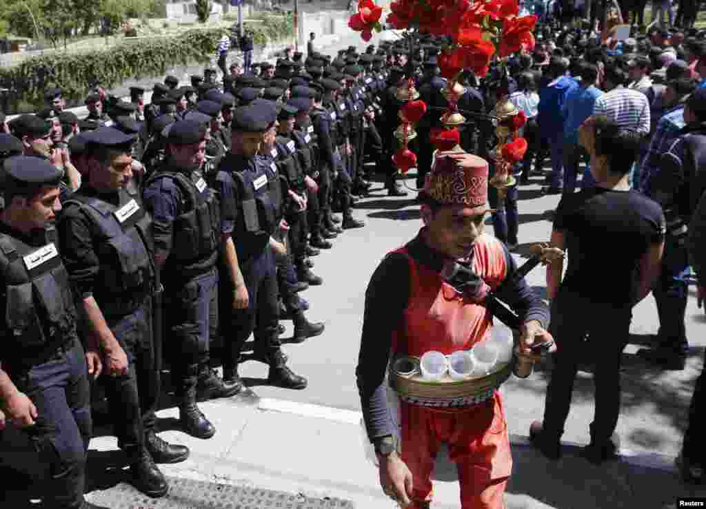 A Palestinian coffee vendor walks past rows of police officers during U.S. President Barack Obama's visit in the West Bank city of Ramallah March 21, 2013.
