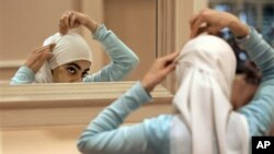 Sadaf Butt, de l'Alabama, ajuste son hijab dans un miroir à la 43e conférence annuelle de la Société islamique d'Amérique du Nord, le 1er septembre 2006, à Rosemont, en Illinois.