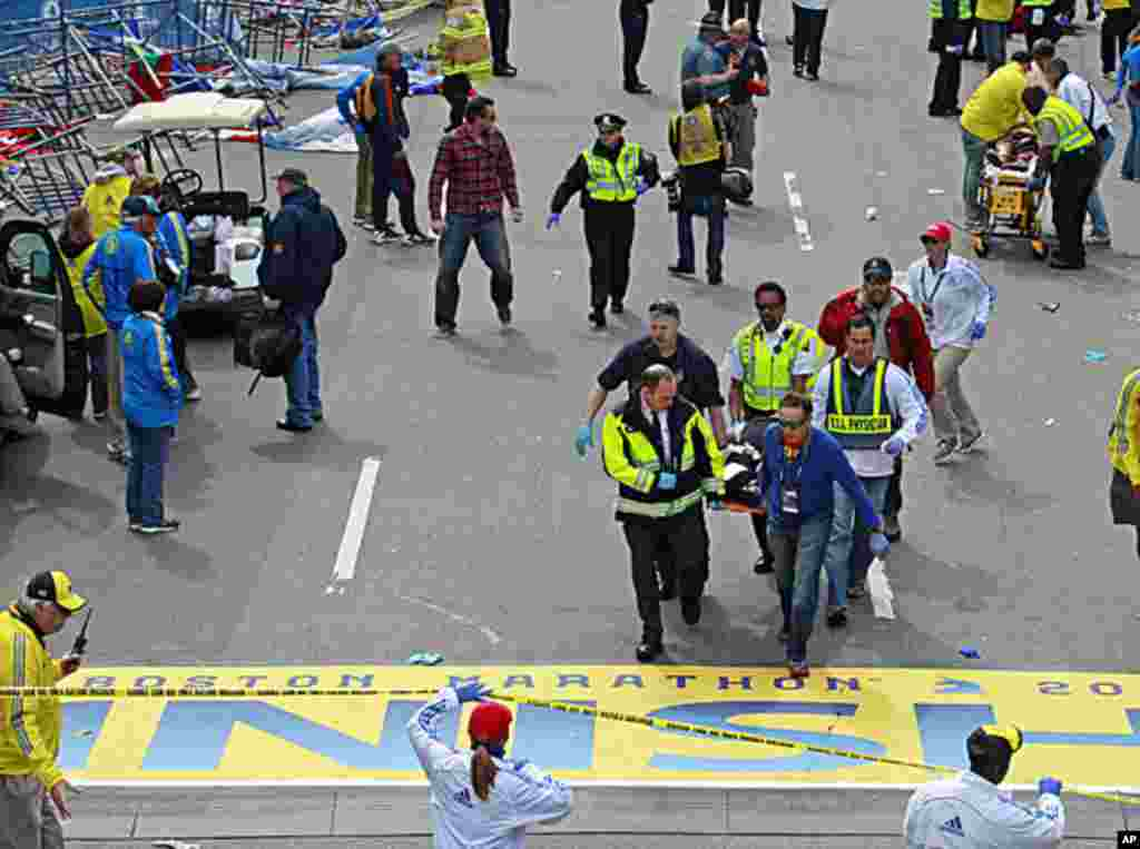 Medical workers transport the injured across the finish line during the 2013 Boston Marathon following an explosion, April 15, 2013.