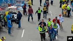 2013年4月15日,波士顿马拉松赛终点附近发生两起爆炸后,医疗救护人员紧急抢救伤者。