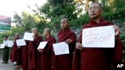 "Buddhist monks hold banners reading ""OIC Get Out"" as they protest against the arrival of a delegation from the Organization of Islamic Cooperation, at the airport in Rangoon, Burma, Nov. 13, 2013."