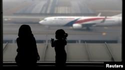 Una mujer y su hija miran la llegad de un avión de Malaysia Airlines llegar al aeropuerto de Kuala Lumpur, Malasia.