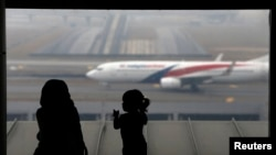 FILE - A woman and a girl look at a Malaysia Airlines plane on the tarmac of Kuala Lumpur International Airport.