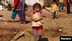 FILE - A girl carries bread outside the tents in the Bab Al-Salam refugee camp in Azaz, Oct. 27, 2014.