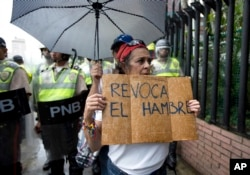"FILE - In this July 27, 2016, file photo, a woman holds a sign with a message that in reads in Spanish ""Revoke hunger"" during a protest march in Caracas, Venezuela."