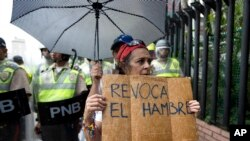 """FILE - A woman holds a sign with a message that in reads in Spanish """"Revoke hunger"""" during a protest march in Caracas, Venezuela, July 27, 2016."""
