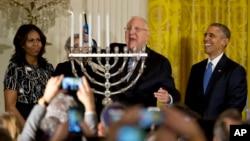 바락 오바마 대통령(오른쪽)과 미셸 오바마 여사(왼쪽)가 9일 백악관에서 루우벤 리블린 이스라엘 대통령(가운데)과 함께 유대인의 명절인 '하누카' 축하 행사를 하고 있다.