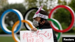 Anti-Olympics protester shows off a placard in front of the Olympic rings monument outside the Japanese Olympic Committee headquarters during their rally, amid the coronavirus disease (COVID-19) outbreak, in Tokyo, Japan May 18, 2021. REUTERS/Issei Kato