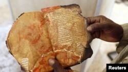 Un agent du Centre Ahmed Baba à Tombouctou montre un manuscrit ancien brûlé