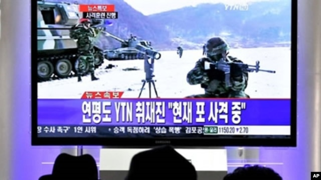 South Koreans watch a live TV breaking news about South Korea's live fire artillery at Seoul train station in Seoul, 20 Dec 2010