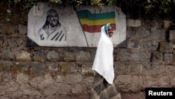 FILE: An Ethiopian woman walks past a mural depicting Ethiopia's Emperor Tewodros II in Addis Ababa, Ethiopia, June 1, 2007.