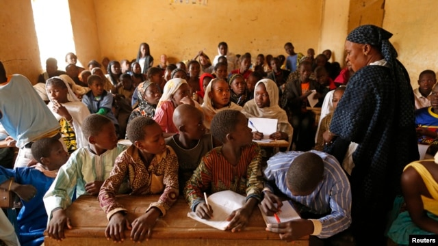 Children listen to a school teacher after the reopening of Mahamane Fondogoumo elementary school in the town center of Timbuktu, Feb. 1, 2013.