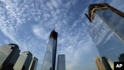 One World Trade Center, center, rises above the National September 11 Memorial and Museum at the World Trade Center, Thursday, Sept. 6, 2012 in New York. Tuesday will mark the eleventh anniversary of the terrorist attacks of Sept. 11, 2001. The World Fina