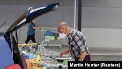 Stanovnik Krajstčerča na Novom Zelandu nosi zaštitnu masku pri odlasku u prodavnicu.