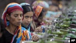 In this Saturday, Dec. 8, 2012, photo, Bangladeshi garment workers manufacture clothing in a factory on the outskirts of Dhaka, Bangladesh.