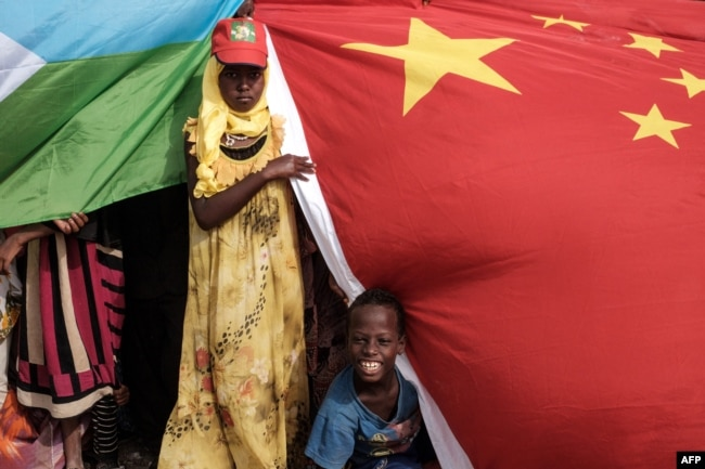 People hold Chinese and Djiboutian national flags as they wait for the arrival of Djibouti's president, Ismaïl Omar Guelleh, before the launching ceremony of new 1,000-unit housing construction project in Djibouti, July 4, 2018. The project is financially supported by China Merchant, the operation partner of newly inaugurated Djibouti International Free-Trade Zone.