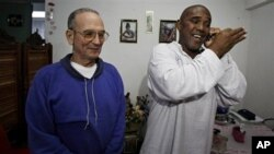 Cuba's dissident Angel Moya, right, speaks on the phone next to fellow dissident Hector Maseda, left, after being released from jail in Havana, Cuba, February 12, 2011.