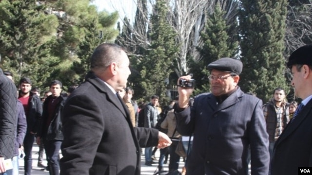 Baku State University security official confronts VOA Azerbaijan service freelancer Tapdig Farhadoglu as he attempts to cover student protest, Baku, Feb. 20, 2014.