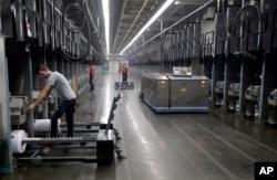 Para pekerja mengganti gulungan benang saat robot mengambil benang yang terbuat dari botol plastik daur ulang di perusahaan tekstil di Yadkinville, North Carolina.