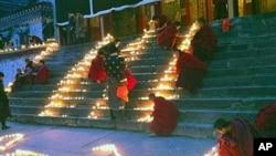 中國四川阿壩藏族羌族自治州的僧侶1月23日在一所寺廟點燃蜡燭為藏人祈福