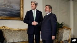 U.S. Secretary of State John Kerry shakes hands with Egyptian President Mohamed Morsi at the Presidential Palace in Cairo, Egypt, March 3, 2013.
