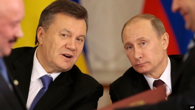 Russian President Vladimir Putin, right, and his Ukrainian counterpart Viktor Yanukovych, left, react after signing an agreement in Moscow, Dec. 17, 2013.