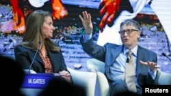 Bill Gates, Co-Chair of the Bill & Melinda Gates Foundation, gestures next to his wife Melinda French Gates during the session 'Sustainable Development: A Vision for the Future' in the Swiss mountain resort of Davos, Switzerland, Jan. 23, 2015.